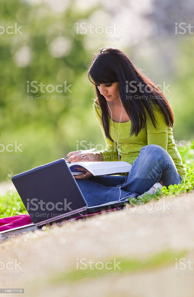 Asian/Indian Student Studying Outside royalty-free stock photo