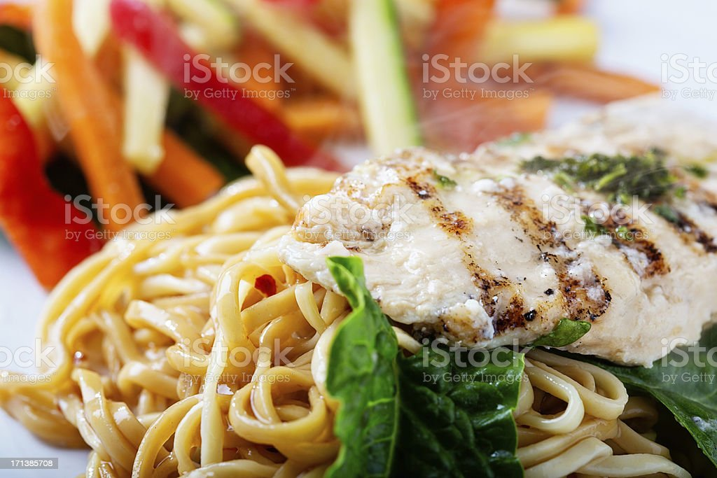 Asian-inspired meal of noodles,grilled chicken and vegetable stir fry royalty-free stock photo