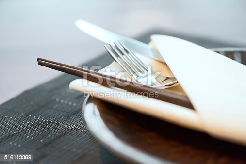 Classy place setting for trendy Asian-Western fusion cuisine - chopsticks, fork, and knife in a folded napkin.  Hong Kong, China.