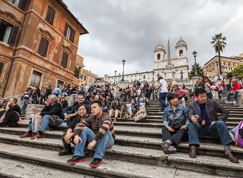 Rome, Italy - November 3, 2012: Trinita dei Monti Church and Spanish Steps in Rome, crowded with tourists. A family of tourists sitting on the steps during a visit in Rome, Italy