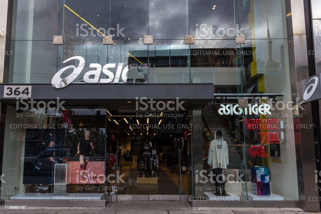 Asics logo in front of their local store in downtown Toronto, Ontario. Asics is a japanse sportswear and footwear brand specialized in shoes stock photo