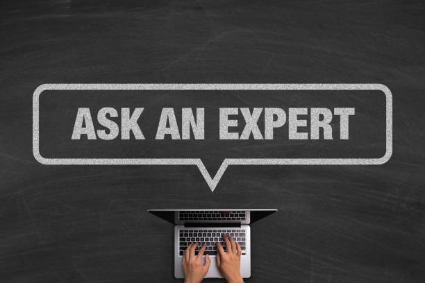 Ask An Expert Concept With Laptop On Blackboard stock photo
