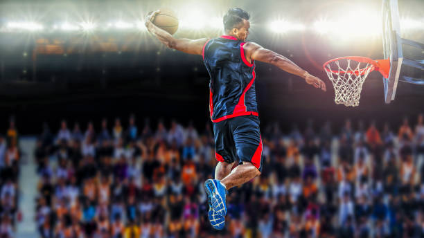 asketball player scoring an athletic slam dunk shoot - sports event stock photos and pictures