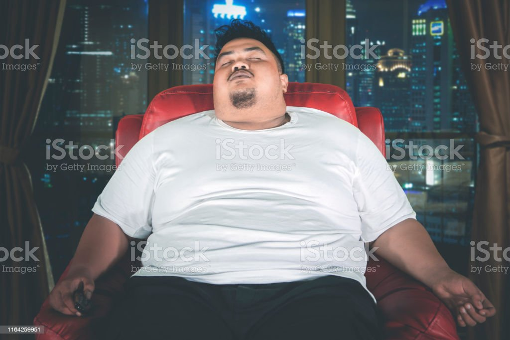 Picture of an obese man falling asleep on the armchair during...
