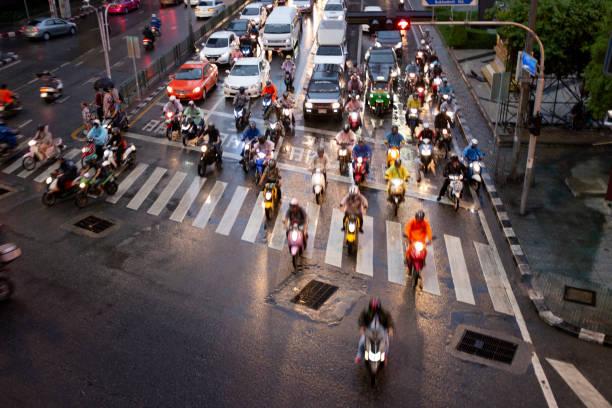 asok sukhumvit junction at night in bangkok, thailand - motorbike, umbrella stock photos and pictures