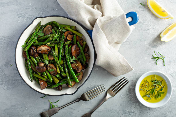 Asparagus and mushrooms in a cast iron pan stock photo