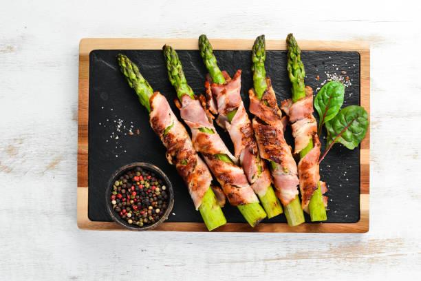 Espargos cozidos com bacon e especiarias. Comida saudável. Vista de cima. Espaço livre para o seu texto. - foto de acervo