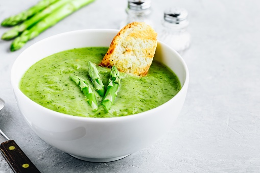 Asparagus cream soup with croutons on gray stone background.