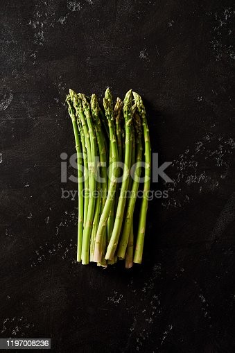 Dozen of asparagus are placed on a black background.