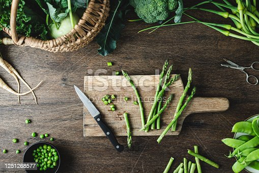 Top view of asparagus on a wooden chopping board with kitchen knife on wooden table. Cutting asparagus on a chopping board in kitchen.