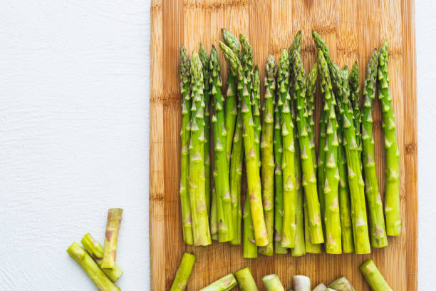 Asparagus on a Wooden Chopping Board, Top View, Close Up on White Background. Cooking, Vegetarian, Healthy Eating stock photo