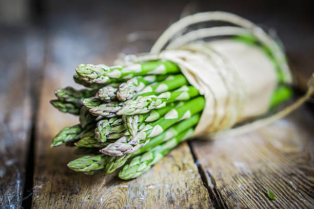 asparagus on rustic wooden background - asparagus stock pictures, royalty-free photos & images