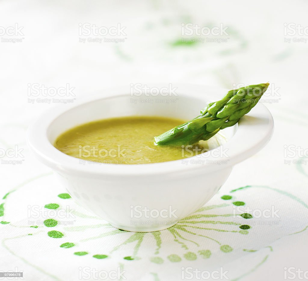 Asparagus spear in white bowl of green soup on tablecloth royalty-free stock photo