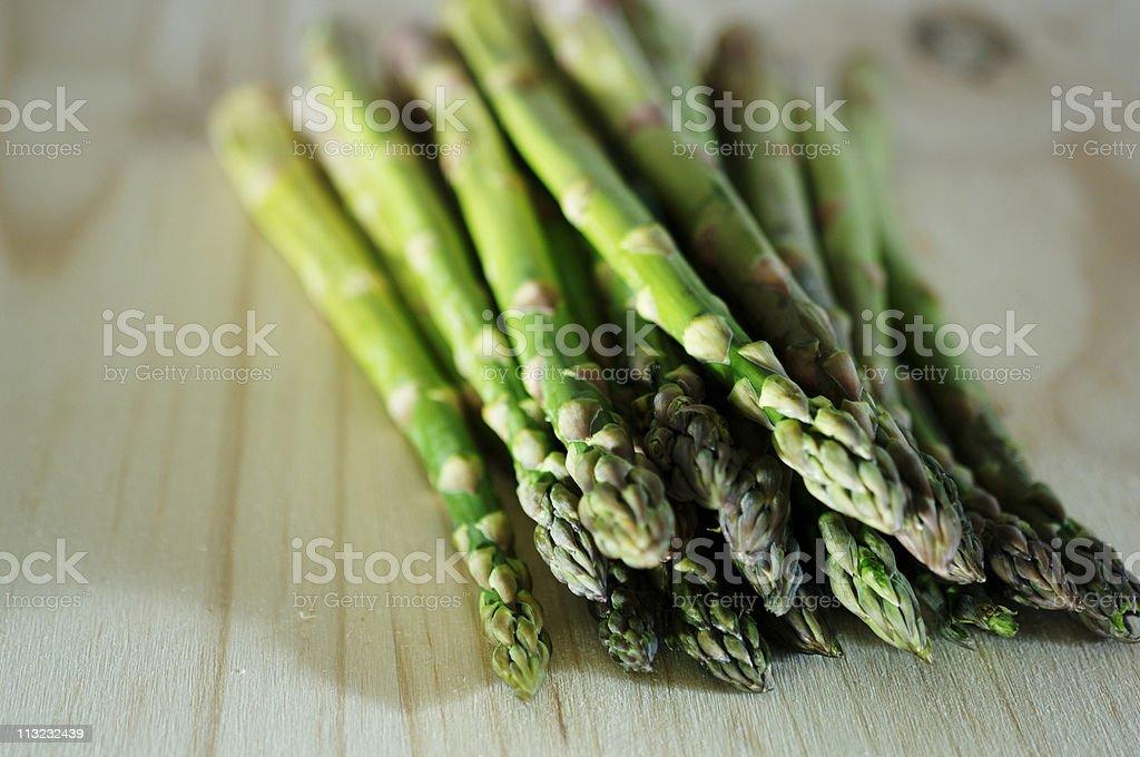 asparagus spears against oak table, rustic farmhouse look royalty-free stock photo