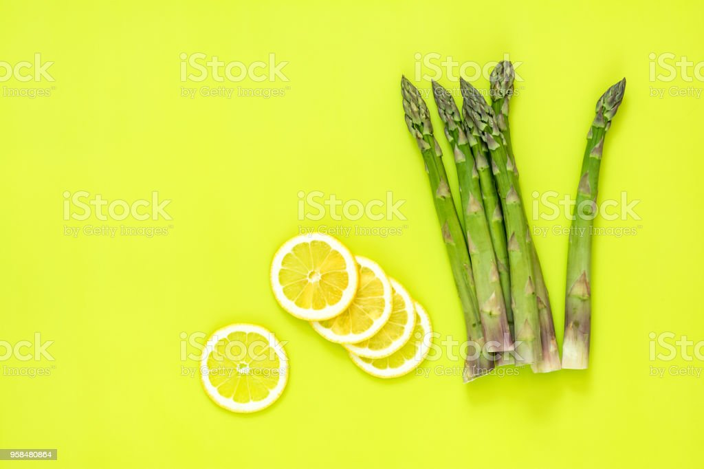 Asparagus sprouts and sliced lemon on bright green surface. stock photo