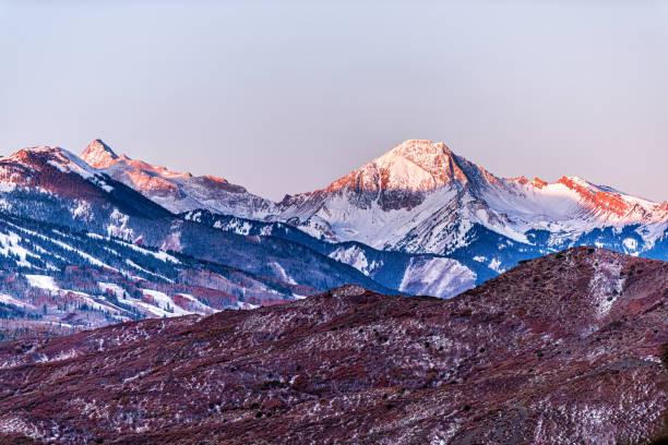 Aspen, Colorado colorful blue sunrise sunlight on Capitol and Mt Daly Snowmass mountain peak ridge closeup silhouette in autumn fall season stock photo
