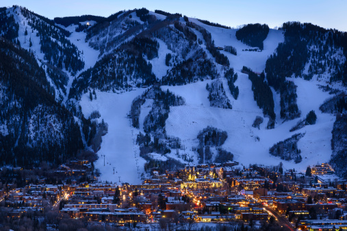 Dusk image of glowing lights in town and cut ski runs and slopes above.  Scenic view with copy space.  Captured as a 14-bit Raw file. Edited in 16-bit ProPhoto RGB color space.