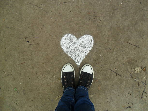 asphalt and feet girls feet in sneakers chalk drawing stock pictures, royalty-free photos & images