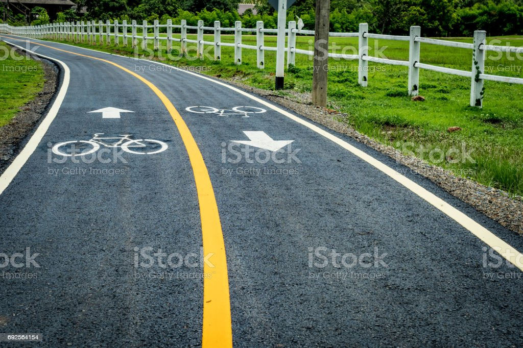 Asphalt bicycle road with yellow line stock photo