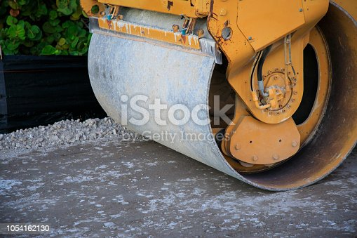 Asphalt compactor roller on some unpaved gravel surface.