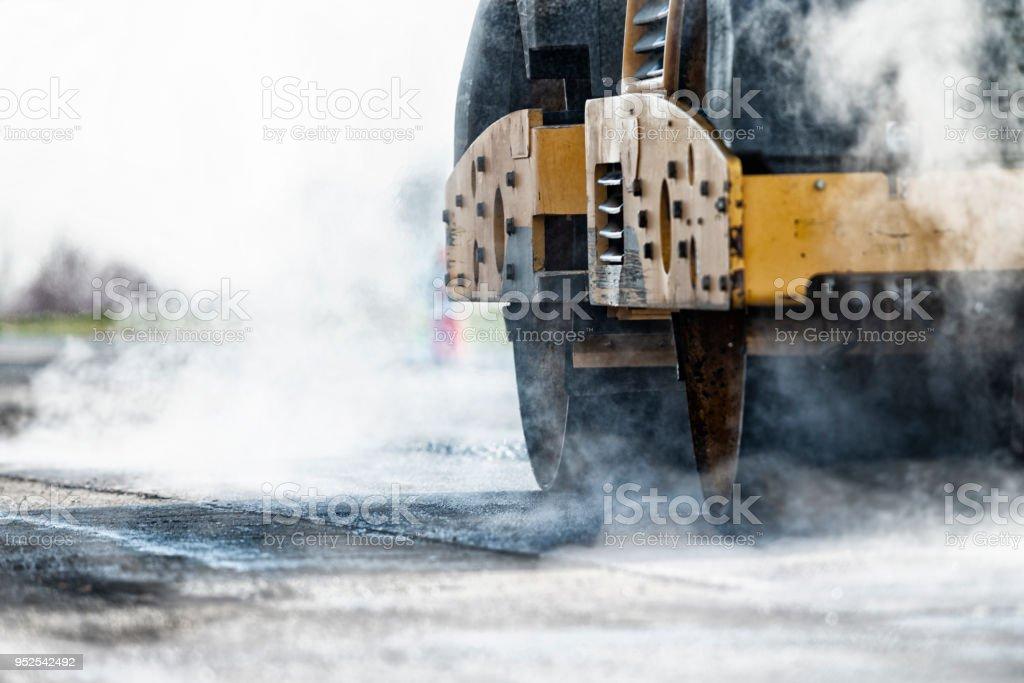 Asphalt-Walzenzug frisch überrollen Asphalt während Oberflächenersatz Projekt gelegt. – Foto