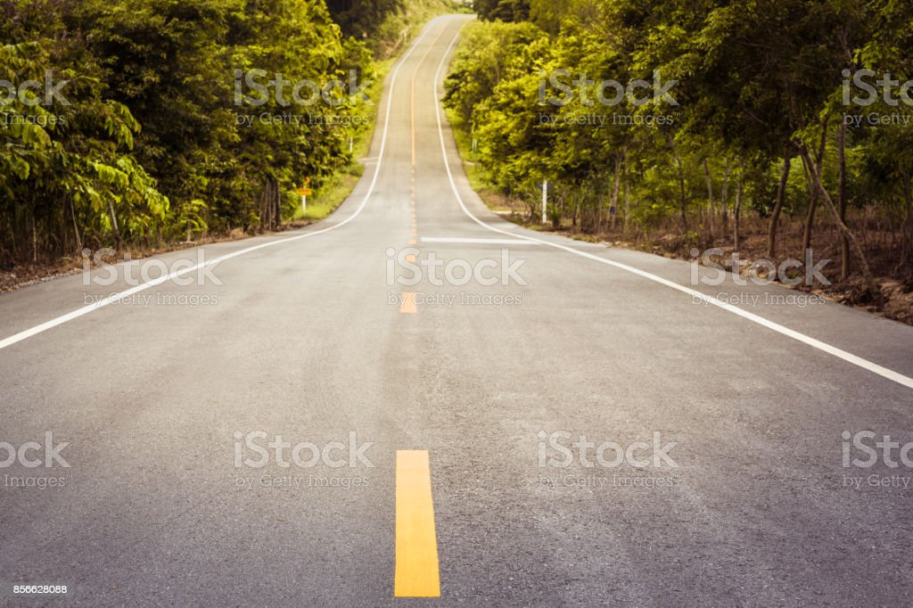 Asphalt concrete road arcoss tropical forest along up to hill with sunlight shining, Concept of journey stock photo