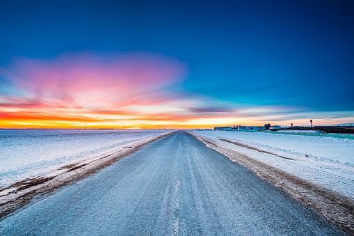 Asphalt Country Open Road Through Winter Snowy Fields And Meadows At Sunset Or Sunrise. Landscape In Belarus Or European Part Of Russia
