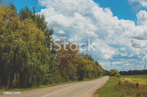 1155573645istockphoto Asphalt country road on a sunny summer day 1095027070
