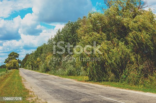 1155573645istockphoto Asphalt country road on a sunny summer day 1095027078