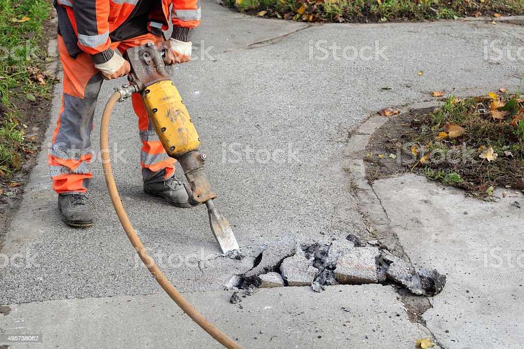 Asphalt demolishing, worker and jackhammer stock photo