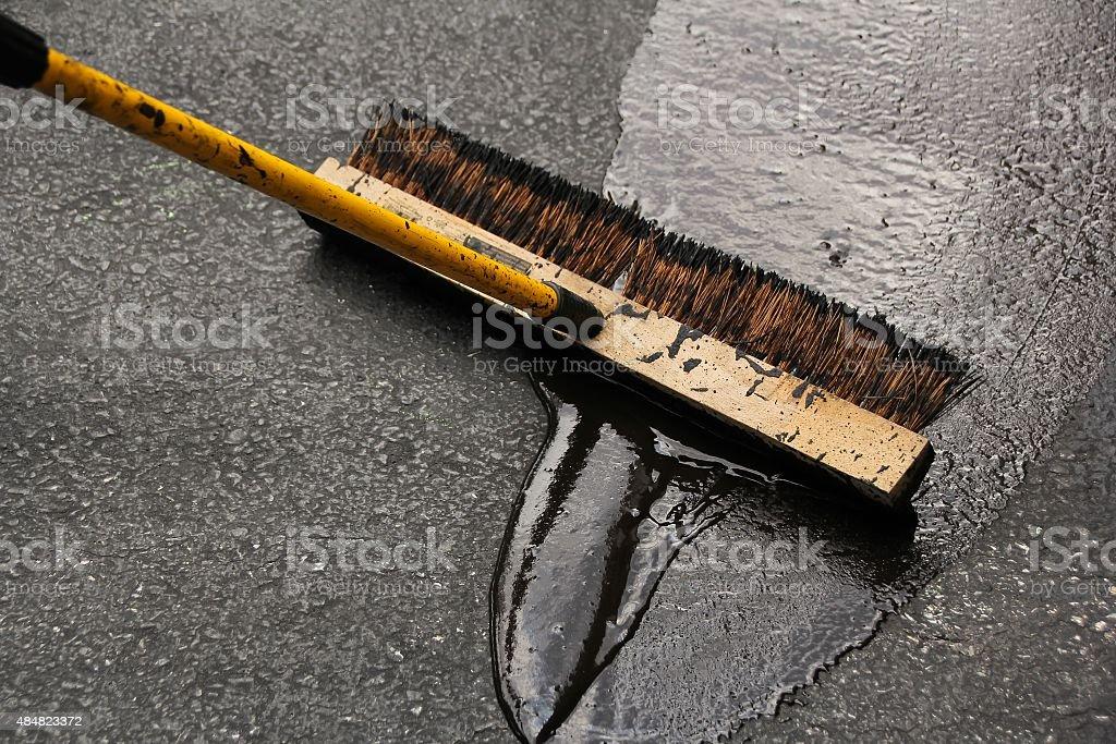 Asphalt driveway sealing with flat brush stock photo