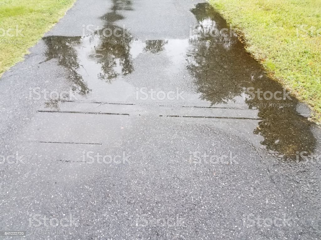 asphalt driveway with large puddles from rain stock photo