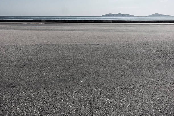 asphalt ground space with seaside background - asphalt stock photos and pictures