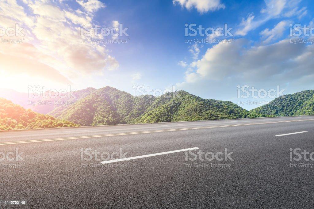 Empty asphalt highway and beautiful natural landscape at sunset