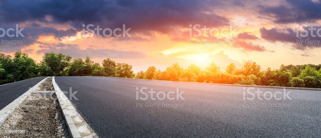 Empty asphalt highway and green forest with beautiful clouds...