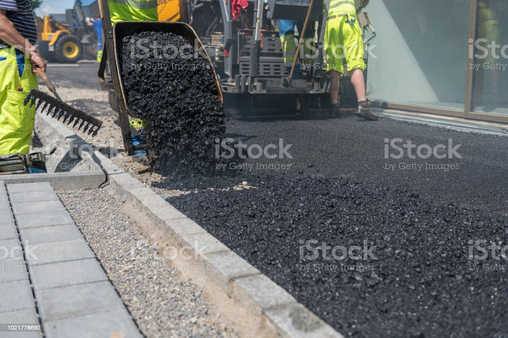 Asphalt is unloaded from a wheelbarrow. The rear part of the asphalt is finished rolled. Asphalt paver in the background. stock photo
