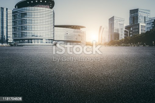 istock Asphalt pavement and modern architecture of city highway 1131704528