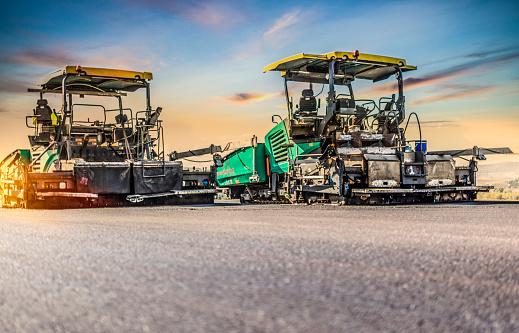 Asphalt paver machines working at sunset