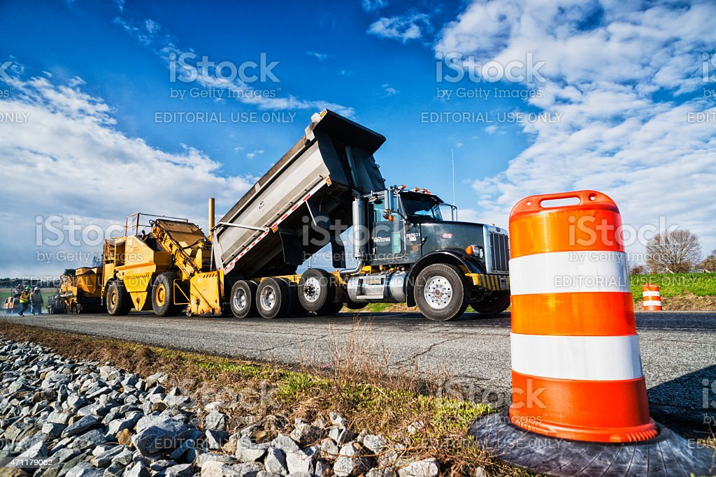 Asphalt paving machinery  resurfacing an old worn road stock photo