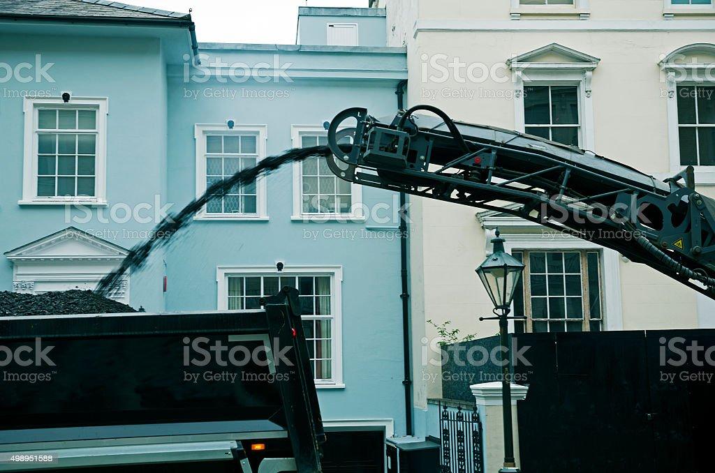 Asphalt projected into dump truck from conveyor belt in London stock photo
