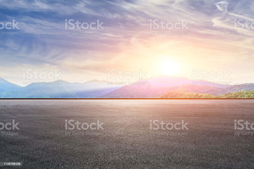 Empty asphalt race track and beautiful natural landscape at sunset