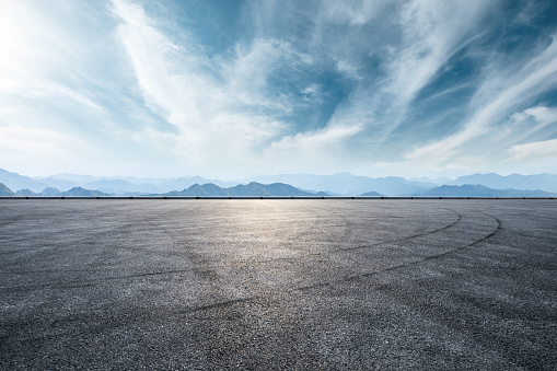 Asphalt race track and mountain with clouds background
