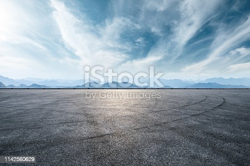 istock Asphalt race track and mountain with clouds background 1142560629
