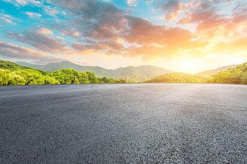 Asphalt race track and mountains with beautiful clouds at sunset