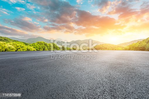 istock Asphalt race track and mountains with beautiful clouds at sunset 1141570349