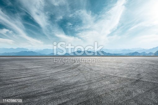 Empty asphalt race track and mountain with clouds background