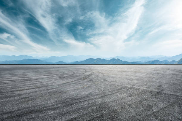 Asphalt race track ground and mountain with clouds background stock photo