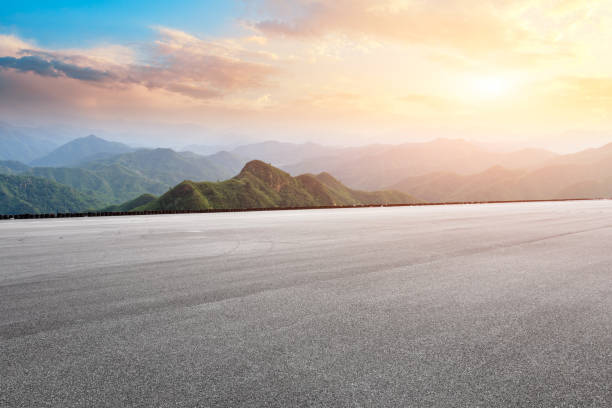 Asphalt race track ground and mountain with sunset clouds stock photo