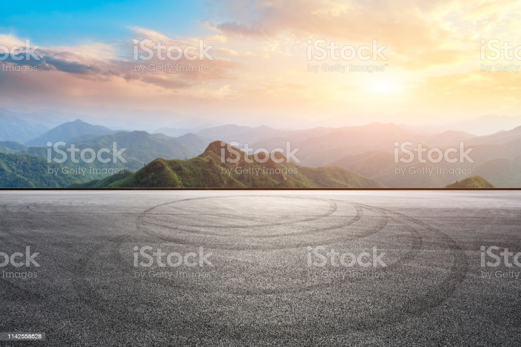 Empty asphalt race track ground and mountain with sunset clouds