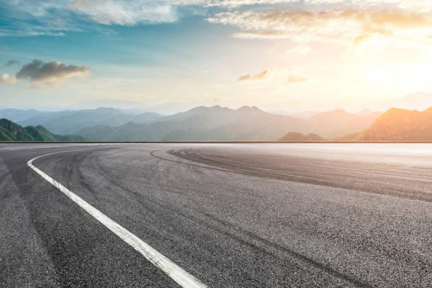 asfalto pista de carreras tierra y montaña con nubes de atardecer - vía fotografías e imágenes de stock